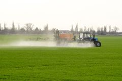 Tracteur avec un dispositif de jet pour l'engrais finement dispersé Photo stock