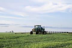 Tracteur avec un dispositif de jet pour l'engrais finement dispersé Tracteur sur le fond de coucher du soleil Le tracteur avec de Images libres de droits