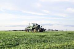Tracteur avec un dispositif de jet pour l'engrais finement dispersé Tracteur sur le fond de coucher du soleil Le tracteur avec de Image libre de droits