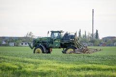Tracteur avec un dispositif de jet pour l'engrais finement dispersé Tracteur sur le fond de coucher du soleil Le tracteur avec de Photo libre de droits