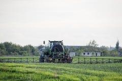 Tracteur avec un dispositif de jet pour l'engrais finement dispersé Tracteur sur le fond de coucher du soleil Le tracteur avec de Photos libres de droits