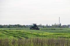 Tracteur avec un dispositif de jet pour l'engrais finement dispersé Tracteur sur le fond de coucher du soleil Le tracteur avec de Photographie stock libre de droits