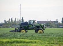 Tracteur avec un dispositif de jet pour l'engrais finement dispersé Tracteur sur le fond de coucher du soleil Le tracteur avec de Photographie stock