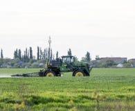 Tracteur avec un dispositif de jet pour l'engrais finement dispersé Tra Image stock