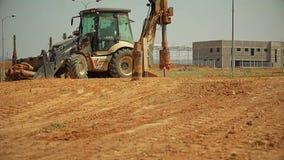 Tracteur avec un dispositif de perçage à un chantier de construction banque de vidéos