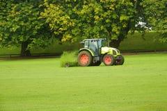 Tracteur avec une herbe de coupe de faucheuse images stock