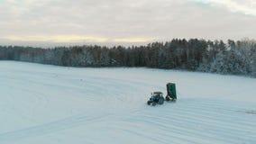 Tracteur bleu avec le corps augmenté de remorque, qui fertilise le sol avec de la farine de dolomite pendant l'hiver pour augment clips vidéos