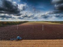 Tracteur cultivant le champ à l'automne Image stock