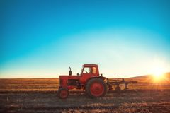 Tracteur cultivant le champ au ressort pendant le coucher du soleil images libres de droits