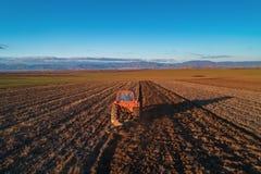 Tracteur cultivant le champ au ressort, vue aérienne photo libre de droits