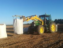 Tracteur déplaçant de grands sacs des pommes de terre Images libres de droits
