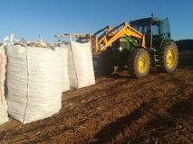 Tracteur déplaçant de grands sacs des pommes de terre Photos libres de droits