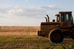 Tracteur dans un domaine frais de foin de coupe Photos stock