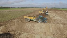 Tracteur de bouledogue d'Erial avec le chargeur de remorque entraînant une réduction un champ clips vidéos