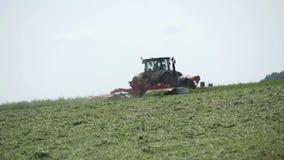 Tracteur de ferme se déplaçant sur le champ agricole pour moissonner la terre Machines agricoles sur moissonner le champ banque de vidéos