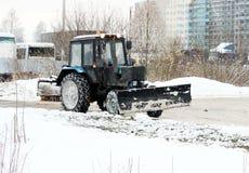 Tracteur de neige en hiver Élimination avec une brosse ronde Photographie stock libre de droits