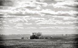 Tracteur et foret d'ensemencement sur un champ Photos stock