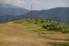 Tracteur fonctionnant au champ sur des collines Photographie stock libre de droits