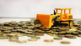 Tracteur jaune ratissant vers le haut des pièces de monnaie Rouble russe images stock