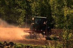 Tracteur labourant au temps de coucher du soleil Photos stock