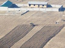 Tracteur labourant la terre sous des cultures d'hiver Image libre de droits
