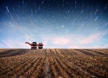 Tracteur labourant le champ de ferme en vue de la plantation de ressort Ciel étoilé fantastique et la manière laiteuse Image stock