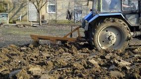 Tracteur labourant le sol dans le jardin clips vidéos