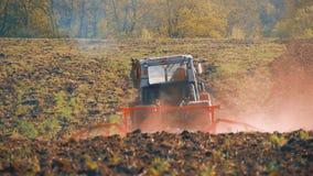 Tracteur préparant la terre avec le cultivateur de semis en tant qu'élément des activités pré de ensemencement des travaux agrico banque de vidéos