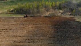 Tracteur puissant en rouge avec la charrue, fonctionnement, labourant, traitement de sol fonc? contre le contexte de sc?nique ren banque de vidéos