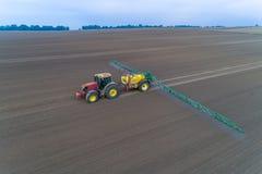 Tracteur pulvérisant les pesticides sur le champ Image stock