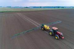 Tracteur pulvérisant les pesticides sur le champ Photo stock