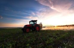 Tracteur pulvérisant un champ à la ferme au printemps image libre de droits