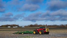 Tracteur rouge de ferme avec le cultivateur vert sur le champ moissonné en automne photos libres de droits