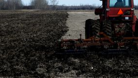Tracteur rouge de ferme tirant le cultivateur indiquant le sol noir sur le champ après récolte des haricots de soja banque de vidéos