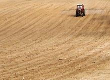 Tracteur rouge sur le champ labouré Photo stock