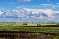 Tracteur sur le champ avec des collines dessus loin photos stock