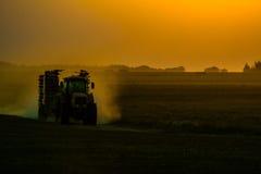 Tracteur sur le champ pendant le coucher du soleil photos libres de droits
