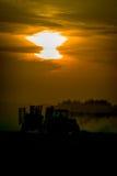Tracteur sur le champ pendant le coucher du soleil Image stock