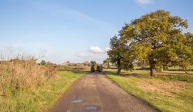 Tracteur sur un chemin de pays un jour ensoleillé de novembre d'automne Image stock