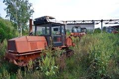 Tracteurs à chenilles envahis rouillés abandonnés Photos stock