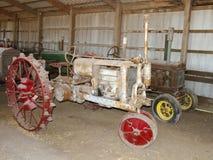 Tracteurs antiques dans une vieille grange Photographie stock