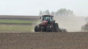 Tracteurs de ferme se d?pla?ant sur le champ agricole pour labourer la terre Tracteur agricole labourant le champ de ferme banque de vidéos