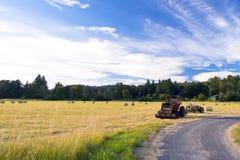 Tracteurs sur le champ pendant la fenaison Photographie stock libre de droits