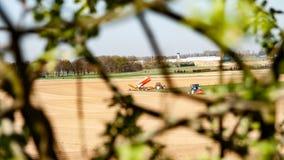 Tracteurs travaillant aux terres cultivables pour planter des légumes vus par les branches d'un arbre images stock
