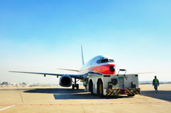 Traction aircraft equipment and aircraft. Traction aircraft equipment is pushing the plane took off at the airport runway Stock Images