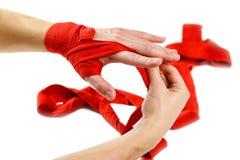 Tractions sur le rouge enfermant dans une boîte en main des bandages Noeuds sur des sports de mains image libre de droits