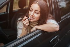 Tractive woman apply pink lipstick in front of rearview mirror in car. Close up Hand. Autumn concept. Autumn forest royalty free stock image