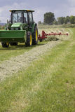 Tracto with rake. Tractor moving forward while raking the field of hay Stock Image