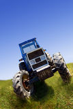 Tractor. Blue tractor parked in a hay field or meadow on a significant slope, blue sky stock photography