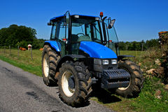 Tractor. Blue tractor on road Stock Photos